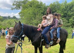 Famillien Strand hadde med hest, som m.a. Iselin Flatebø Hovland og borna f.v. Liv, Isak og Nour fekk ri på. Det er Anne Sofie Strand som held i taumane til hesten.