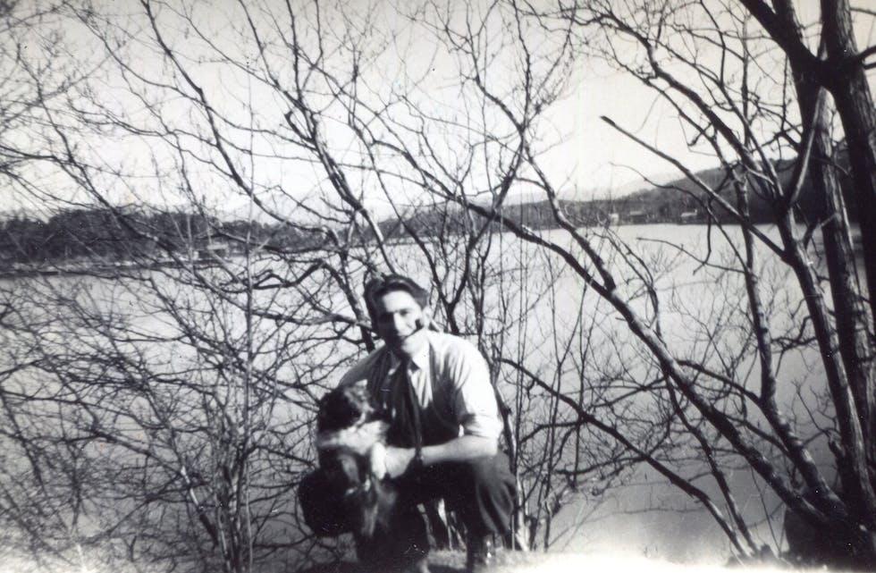 Olav Bøe (1925-2009) med pipe og hund. Ålfjorden i bakgrunnen.